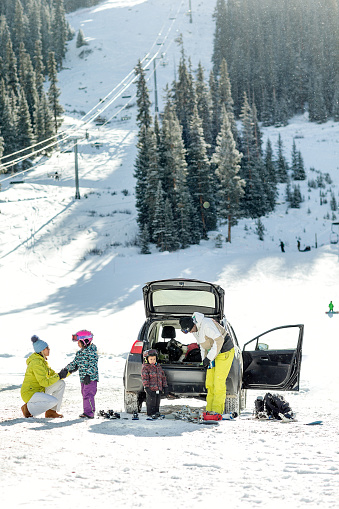 Multi-racial family at a winter ski resort, unloading gear and parents helping kids with their outfits. - gettyimageskorea