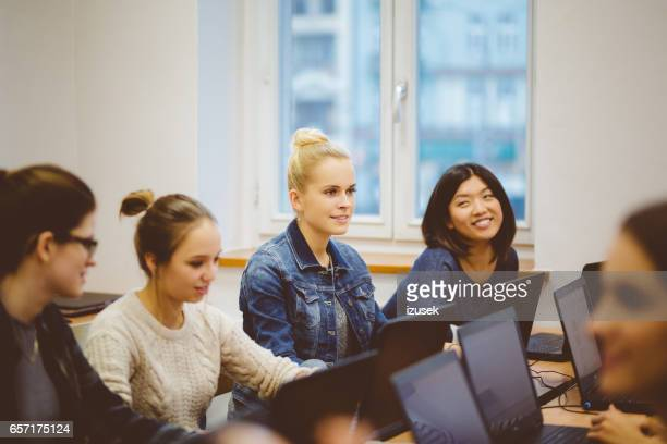 Multiracial female students at computer programming class
