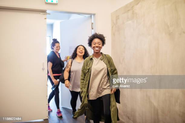 multiracial females entering fitness studio - studio workplace stock pictures, royalty-free photos & images