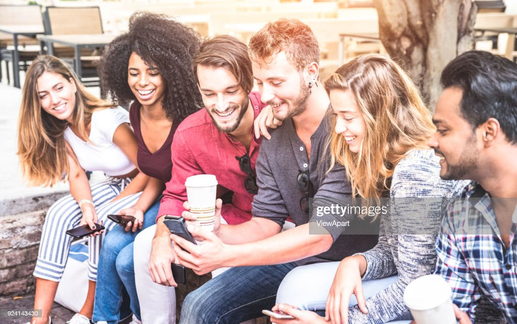 Multiracial friends group using smartphone at university college - Young people addicted by mobile smart phone - Technology concept with connected trendy millennials - Soft pink pastel sunshine filter : Stock Photo