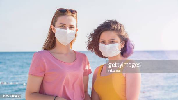 multiracial friends smiling with face mask after lockdown reopening - new normal friendship concept with guys and girls having fun together on travel vacation - bright filter with focus on right woman - good; times bad times stock pictures, royalty-free photos & images
