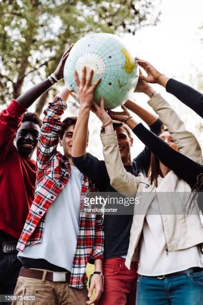 amici multirazziali con il globo al parco - mondo beat foto e immagini stock