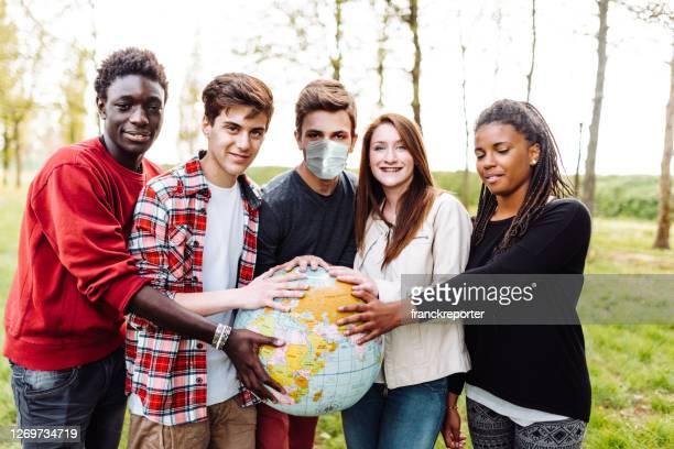 amici multirazziali con il globo durante il covid - mondo beat foto e immagini stock