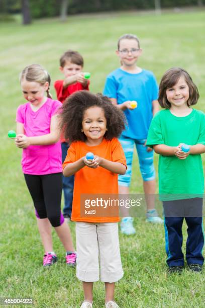 multiracial group of children in an egg spoon race - african american easter stock photos and pictures