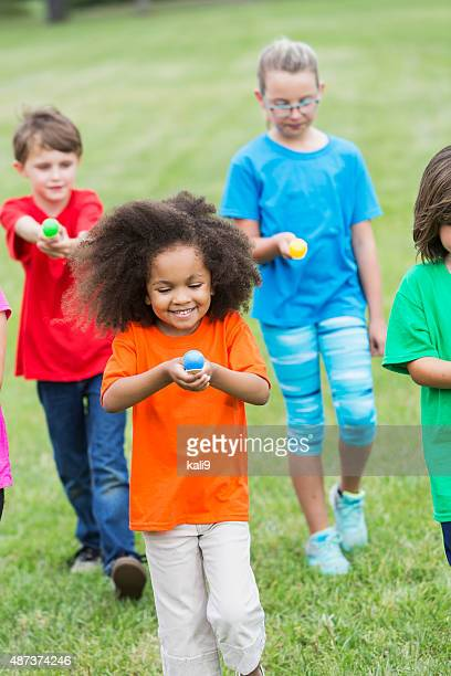 Multiracial group of children in an egg spoon race