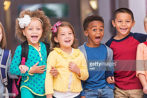 multiracial group of children in preschool hallway - children only stock pictures, royalty-free photos & images