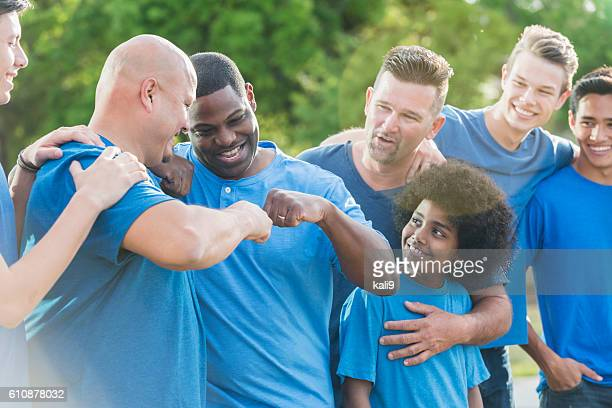 Multi-racial group of fathers and sons in blue shirts