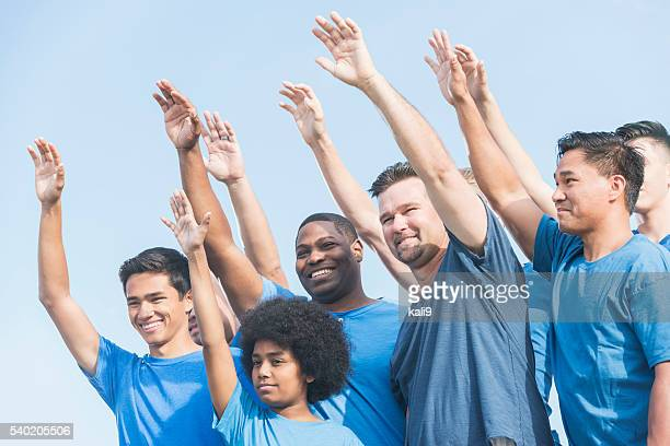 Multiracial group of fathers and sons raising hands