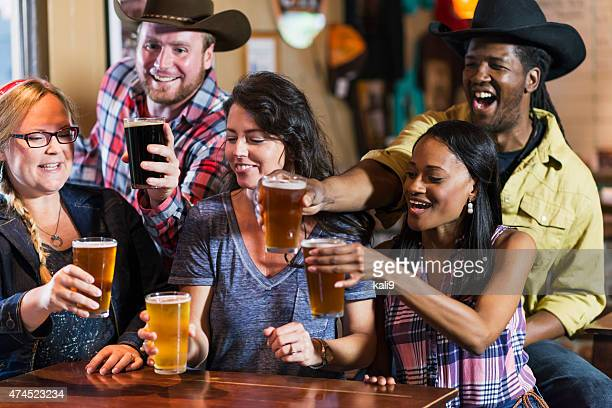 Multiracial group of friends drinking beer, toasting