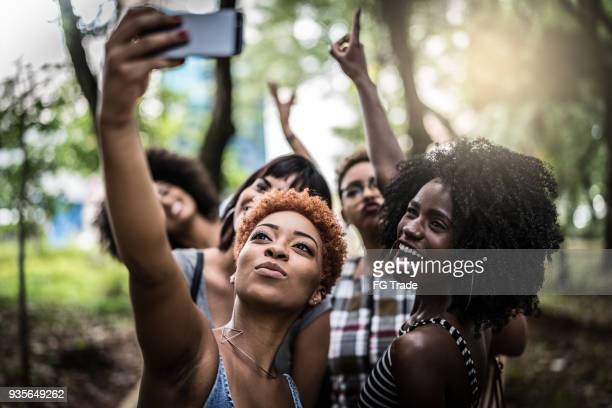 multiracial group of friends taking selfie - popolo di discendenza africana foto e immagini stock