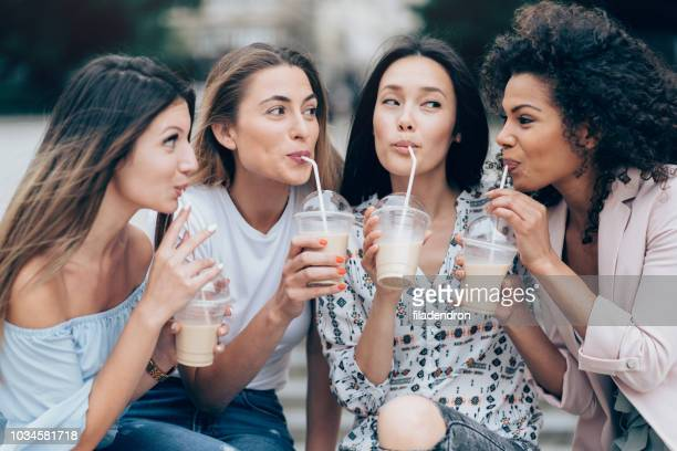 multiracial group of girlfriends drinking ice coffee - iced coffee stock pictures, royalty-free photos & images