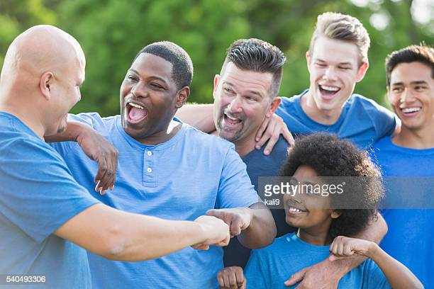 Multi-racial group of men and sons, fist bump