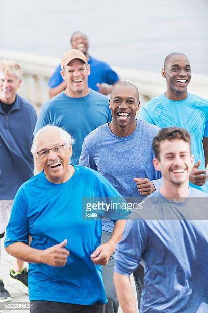 multiracial group of men in blue shirts running - african american man helping elderly stock pictures, royalty-free photos & images