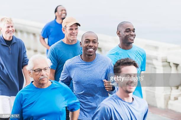 Gruppe von Personen verschiedener Herkunft der Männer in blauen Hemden running