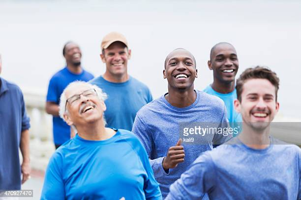 multi-racial group of men wearing blue shirts - african american man helping elderly stock pictures, royalty-free photos & images