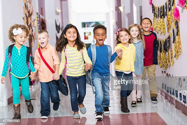 multiracial group of preschoolers running down hallway - preschool building stock pictures, royalty-free photos & images