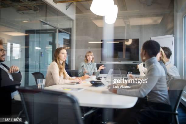 multiracial group of professionals having meeting - binnenin stockfoto's en -beelden