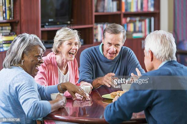 Multiracial group of seniors talking over coffee