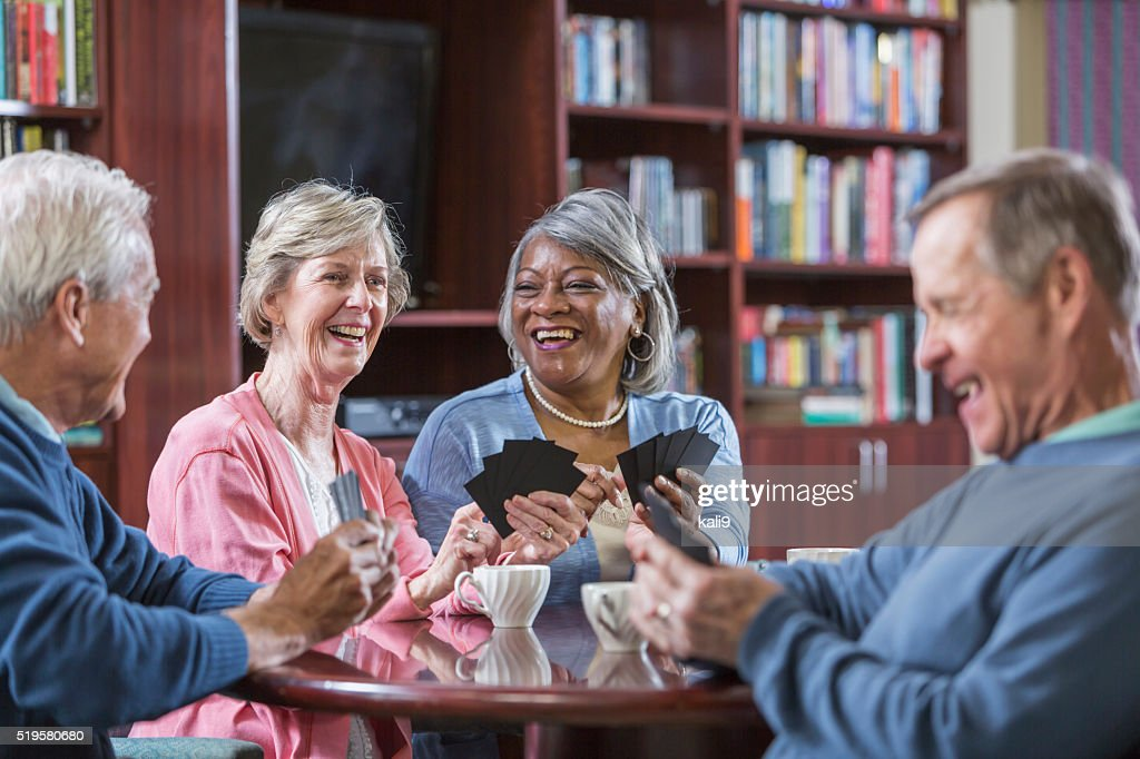 Multiracial group of seniors talking, playing card game : Stock Photo