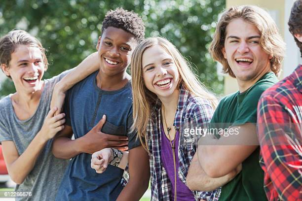 multiracial group of teenagers handing out outdoors - tiener stockfoto's en -beelden