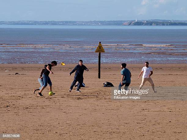 Multiracial group of young men playing football on the beach WestonsuperMare Somerset UK