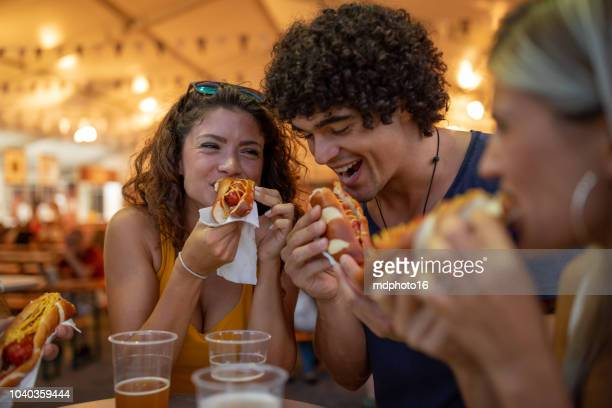 Multiracial happy young people laughing and eating together at carnival