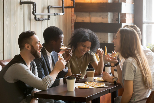 Multiracial happy young people laughing eating pizza together in pizzeria 914989896