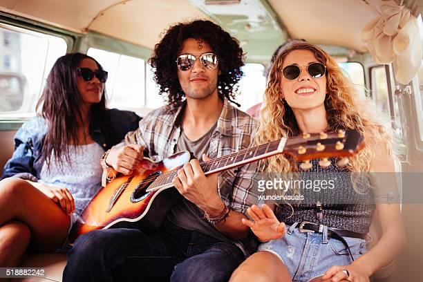 Multi-ethnische Hipster Freunde singen gemeinsam auf Straße Reise mit Gitarre