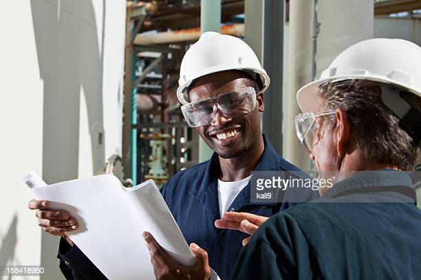 multiracial industrial workers reviewing plans - black jumpsuit stock photos and pictures