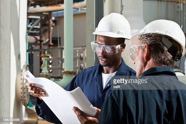 Multiracial industrial workers reviewing plans