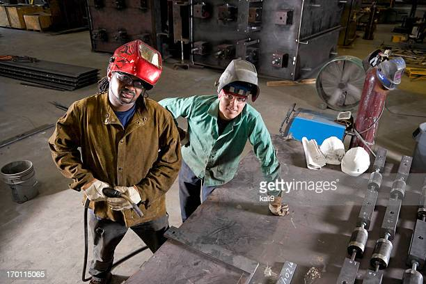 Multiracial industrial workers with welding tools