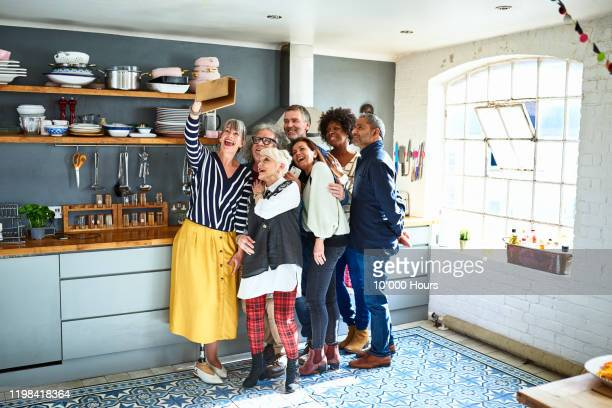 multiracial mature friends taking selfie in kitchen on tablet - 50 54 years stock pictures, royalty-free photos & images