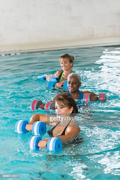 multiracial mature women in water aerobics class - hydrotherapy stock photos and pictures