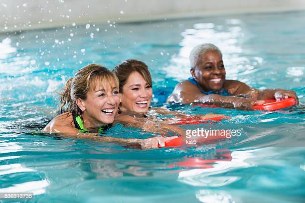 Multiracial middle-aged women swimming in pool