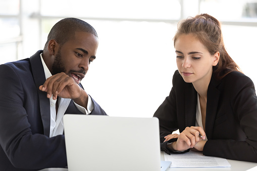 Multiracial millennial team working together in office using laptop 1139630489