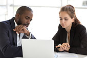Multiracial millennial team working together in office using laptop
