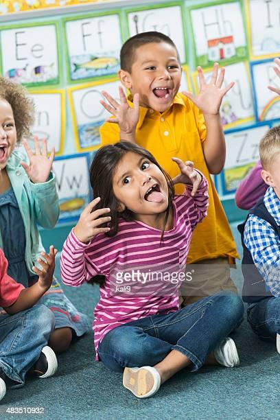 Multiracial preschoolers having fun making faces