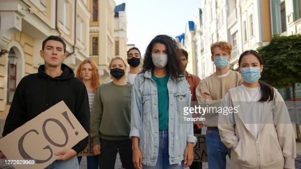 multiracial protest demonstration, protesters wearing medical masks. - protestante imagens e fotografias de stock