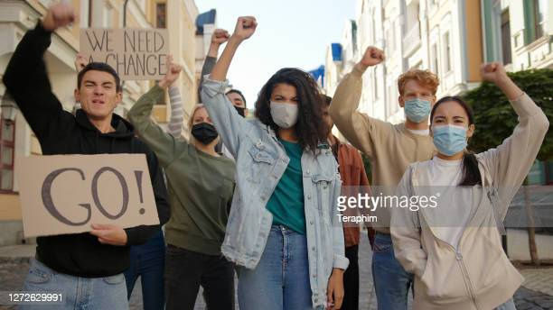 multiracial protest demonstration, protesters wearing medical masks. - anti quarantine protest stock pictures, royalty-free photos & images