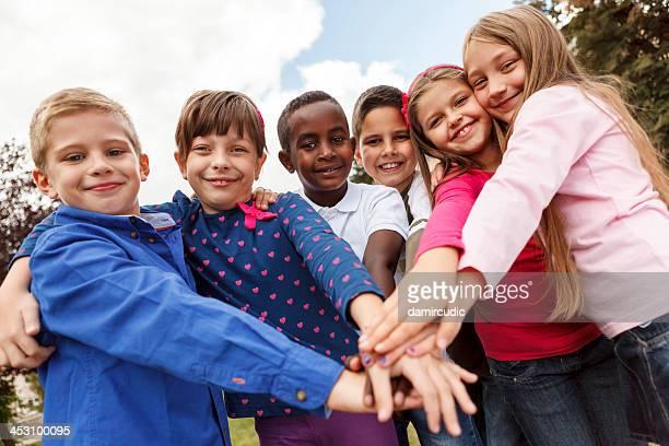 Multiracial school children putting their hands together