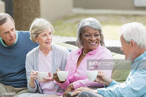 Multiracial senior friends outdoors drinking coffee