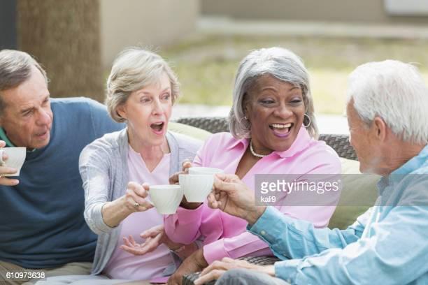 Multirracial sénior amigos a beber café ao ar livre