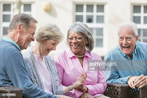 multiracial senior friends sitting outdoors on patio talking - community centre stock pictures, royalty-free photos & images