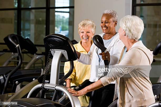 Multiracial senior women in fitness center on elliptical trainer