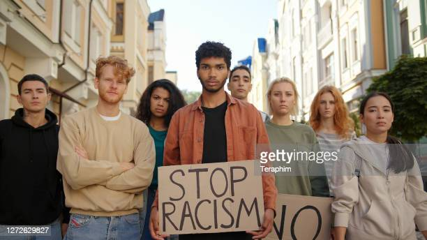 multiracial students on public demonstration at city street against racism with slogans on posters - racism stock pictures, royalty-free photos & images