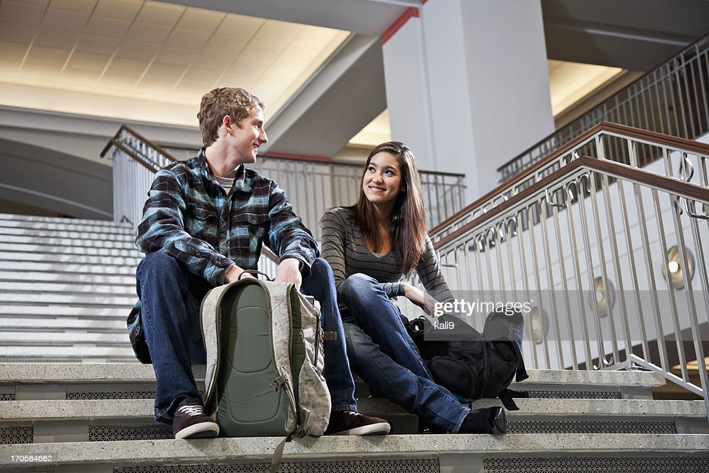 Multiracial students on steps of school building : Stock Photo