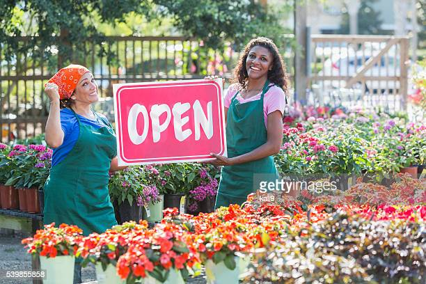 multiracial women holding open sign in garden center - opening ceremony stock pictures, royalty-free photos & images