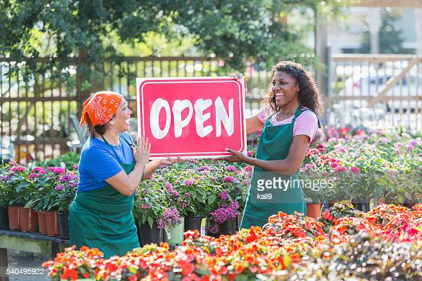 multiracial women holding open sign in garden center - store opening stock pictures, royalty-free photos & images