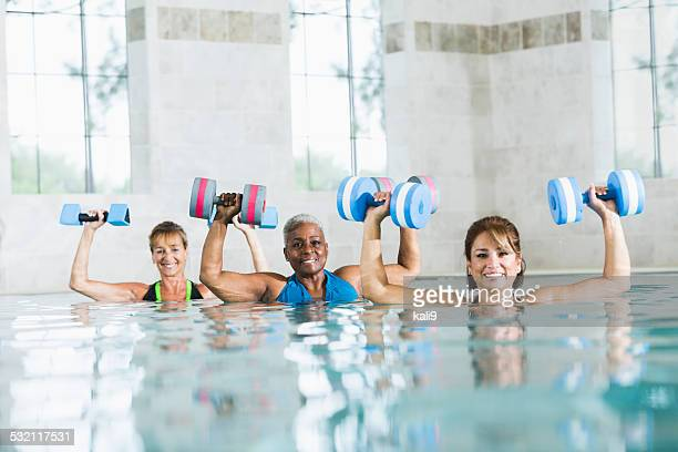 Multiracial women in water aerobics exercise class
