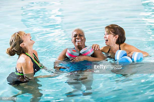 Multiracial women in water exercise class laughing